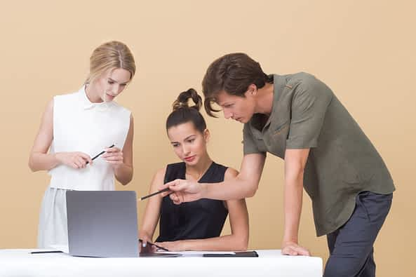 A group of people looking at a computer Funciones-community-manager-laptop-trabajando.jpg.